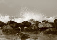 Silent water behind large rocks at beach Stock Photo