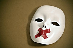 Silent white mask. White mask with red tape strips forming a cross in its mouth on a brown background