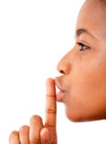 Silently!. Close up of an African woman's finger on her mouth saying be quiet Stock Photography