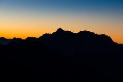Silhoette della montagna delle alpi austriache ad alba Fotografia Stock