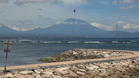 The silhoette of Mount Agung - sleeping Bali volcano, the view from the Sanur beach over the sea with waves. Sunny day, almost no