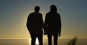 Silhoeutte of couple walking hand in hand on the beach during sunset 4k stock video