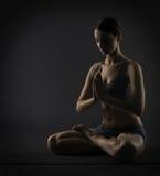 瑜伽妇女思考坐在莲花姿势 Silhoue 免版税库存图片