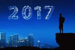 Silhouet Aziatische jonge mens met heldere ster op een 2017 Stock Foto's