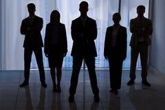 Silhouet bedrijfsmensen die zich in bureau bevinden Royalty-vrije Stock Foto's