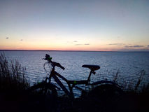 Silhouet a bicycle against the background of grass and sunset over the river or sea stock image
