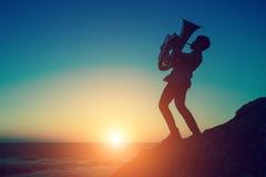 Silhouet bij zonsondergang van een de Tuba muzikaal instrument van het musicusspel op overzeese kust openlucht hobby royalty-vrije stock fotografie