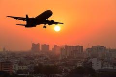 Silhouet commercieel vliegtuig die over stad tijdens zonsondergang vliegen stock afbeeldingen