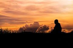 Silhouet - de Boeddhistische Monnik Meditation en wolken die hemel gelijk maken stock fotografie