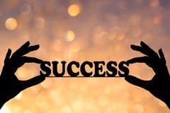 Silhouet, de conceptuele tekst van het bericht 'SUCCES 'in veilige handen Geel en sinaasappel bokeh op de achtergrond stock foto's