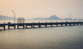 Silhouet die van één mensenzitting alleen op een cementpijler in de afstand, op privé gebied Sattahip, Thailand vissen Stock Afbeelding