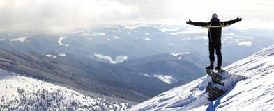 Silhouet die van alleen toerist zich op sneeuwbergbovenkant bevinden in wi royalty-vrije stock foto