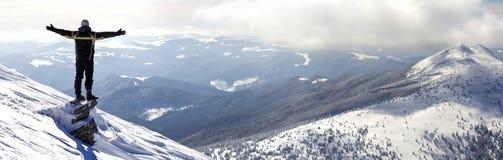Silhouet die van alleen toerist zich op sneeuwbergbovenkant bevinden in wi stock fotografie