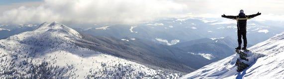 Silhouet die van alleen toerist zich op sneeuwbergbovenkant het bevinden in winnaar stelt met opgeheven handen genietend van meni royalty-vrije stock fotografie