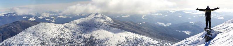 Silhouet die van alleen toerist zich op sneeuwbergbovenkant het bevinden in winnaar stelt met opgeheven handen genietend van meni stock afbeeldingen