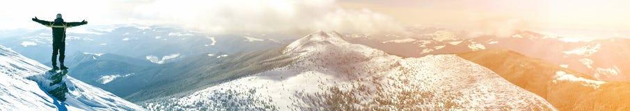 Silhouet die van alleen toerist zich op sneeuwbergbovenkant het bevinden in winnaar stelt met opgeheven handen genietend van meni royalty-vrije stock foto
