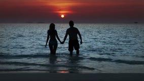 Silhouet die van de man en de vrouw, naar het overzees op een zonsondergang gaan en in golven kussen stock video