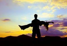 Silhouet die van de mens en vrouw bovenop berg opstaan houden Royalty-vrije Stock Afbeelding