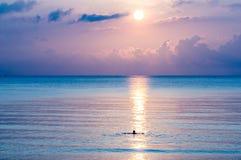 Silhouet die van de mens in het overzees zwemmen Stock Foto