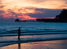 Silhouet die van de Mens zich in de Oceaan bij Zonsondergang bevinden Royalty-vrije Stock Fotografie