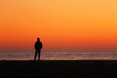 Silhouet die van de mens zich door oceaan bevinden Stock Afbeelding