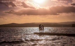 Silhouet die van familie zich aan het eind van pier onder heldere dramatische zonsonderganghemel bevinden royalty-vrije stock afbeeldingen