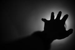 Silhouet die van hand aan licht bereiken Stock Foto's