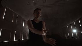 Silhouet die van jonge balletdanser zich terug naar camera bevinden Licht silhouet van elegante jonge ballerina die bevinden zich stock videobeelden