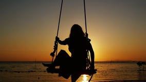 Silhouet die van jonge vrouw op een schommeling door de zon bij mooie zonsondergang op tropisch strand slingeren Langzame Motie stock video