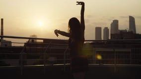 Silhouet die van jonge vrouw op zonsondergang dansen stock video