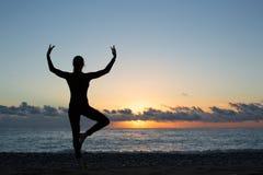 Silhouet die van persoon yoga op het strand doen bij zonsopgang royalty-vrije stock fotografie