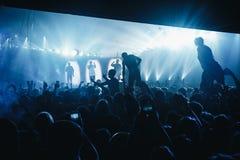 Silhouet die van persoon zich op de menigte met uitgetrokken hand bevinden royalty-vrije stock afbeeldingen