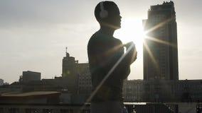 Silhouet die van volwassen vechter vóór gelijke in stralen van zon opwarmen, motivatie stock video
