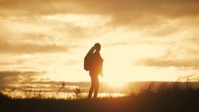 Silhouet die van vrolijke meisjestoerist met rugzak die bij zonsondergang dansen, zich bovenop een berg bevinden Het concept van stock video