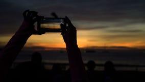 Silhouet die van vrouw beeld van zonsondergang met telefoon nemen bij strand stock video