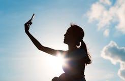 Silhouet die van vrouw selfie met telefoon nemen stock afbeeldingen