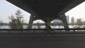 Silhouet die van vrouwelijke fietser een fiets berijden bij zonsondergang onder de brug Cinematic het cirkelen schot stock video