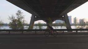 Silhouet die van vrouwelijke fietser een fiets berijden bij zonsondergang onder de brug Cinematic het cirkelen schot Langzame Mot stock video