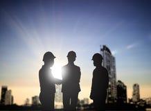 Silhouet drie de achter sprekende Zaken van de menseningenieur in een bui Stock Afbeeldingen