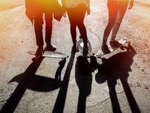 Silhouet drie vriendenskateboarders in stad stock foto's