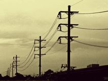 Silhouet, Elektriciteitspost in gouden hemel Stock Fotografie