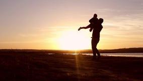 Silhouet, gelukkig kind met moeder en vader, familie bij zonsondergang, zomer Looppas, die baby omhoog in de lucht, omhelzingen o stock videobeelden