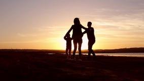 Silhouet, gelukkig kind met moeder en vader, familie bij zonsondergang, zomer Looppas, die baby omhoog in de lucht, omhelzingen,  stock video