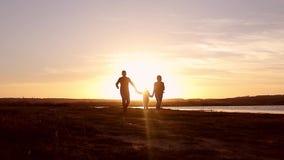 Silhouet, gelukkig kind met moeder en vader, familie bij zonsondergang, zomer Looppas, die baby omhoog in de lucht, omhelzingen,  stock footage