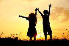 Silhouet, het gelukkige kinderen spelen Royalty-vrije Stock Afbeeldingen