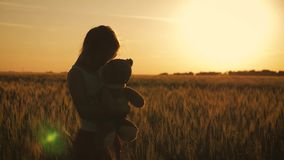 Silhouet het jonge meisje spelen met teddybeer op een tarwegebied bij zonsondergang Concepten grote droom stock footage