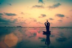 Silhouet jonge vrouw het praktizeren yoga op het strand Royalty-vrije Stock Foto