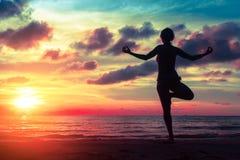 Silhouet jonge vrouw het praktizeren yoga op het strand Royalty-vrije Stock Foto's