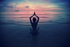 Silhouet jonge vrouw het praktizeren yoga op het strand bij surrealistische zonsondergang royalty-vrije stock afbeeldingen