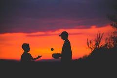 Silhouet 2 jongens die vangst spelen bij zonsondergang royalty-vrije stock foto's
